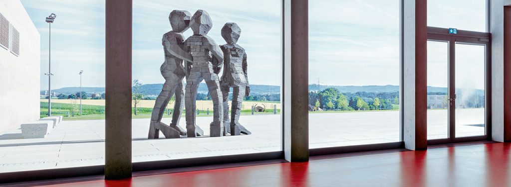 "One striking detail in the foyer of CARMEN WÜRTH FORUM is the skillful interplay between light and shadows. A sculpture garden is located on the square in front of the building, exhibiting the work ""BDM (Group of Girls)"" from the Würth Collection, crafted by Georg Baselitz in 2012."
